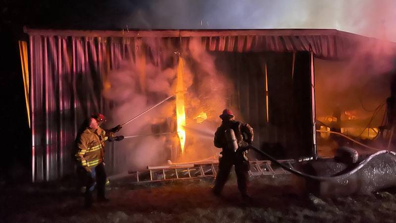 Firefighters extinguish flames at shop.