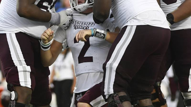 Mississippi State quarterback Will Rogers (2) is helped up by linemen Kwatrivous Johnson, left,...