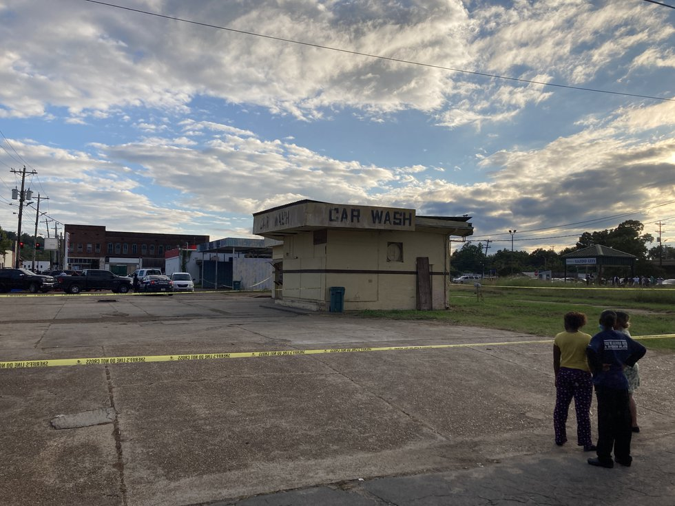 Witnesses look on as officers investigate a crime scene following a double shooting in Yazoo...