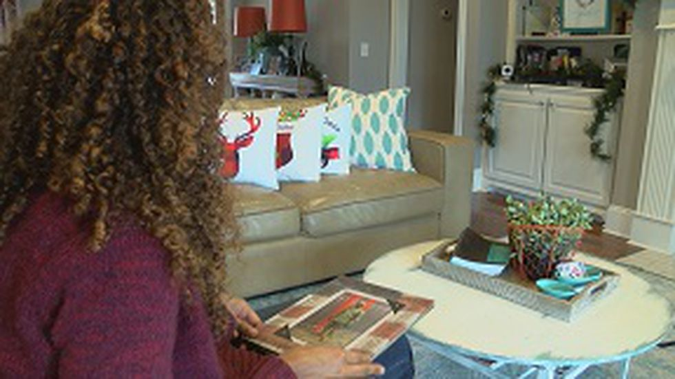Nicole Malley looks at pictures of her husband Carlos Malley, an Army Reservist. (Source: WLBT)