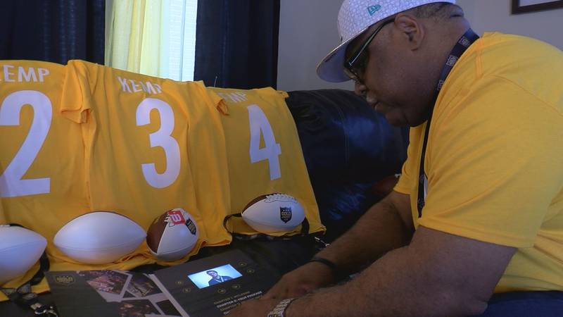 John Kemp looks at an interactive Super Bowl LIV booklet with jerseys ready for he and his...