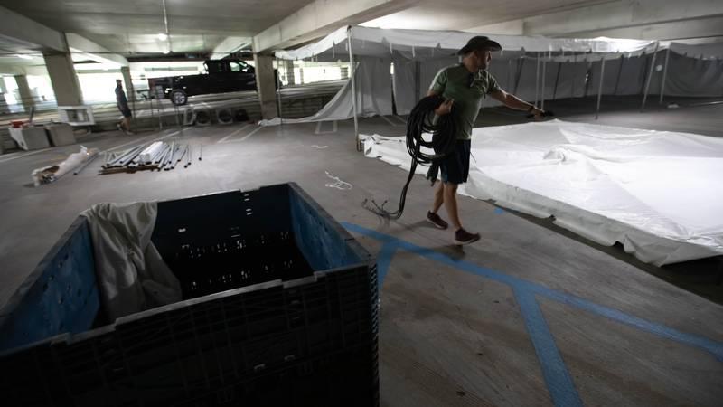 Sunbelt Rentals employee Jarrett England helps set up a field hospital in parking garage B...
