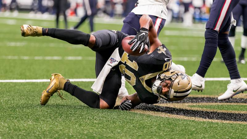 Saints wide receiver Tre'Quan Smith rolls over after catching a touchdown pass from Drew Brees...
