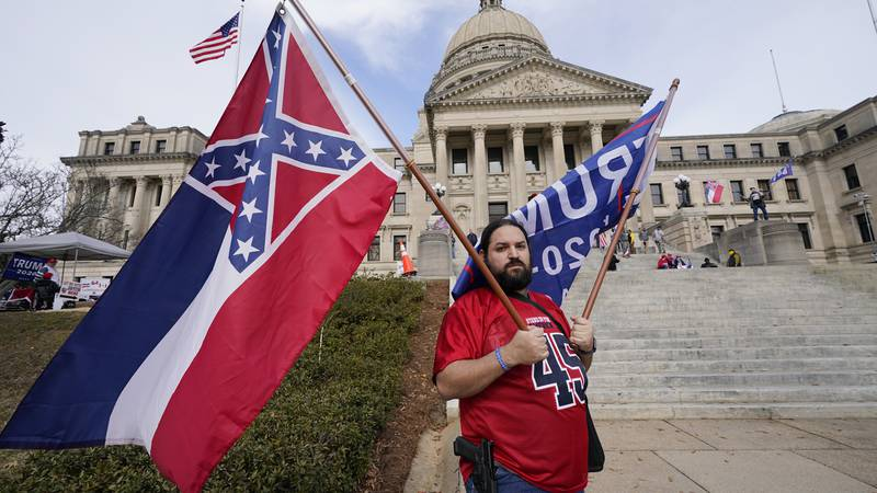 Jason Lavoie of Raymond, carries both the retired Mississippi state flag and a Trump flag as he...