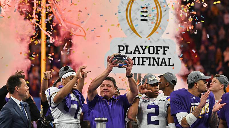 LSU head coach Ed Orgeron raises the Chick-fil-A Peach Bowl Trophy after the Tigers beat the...