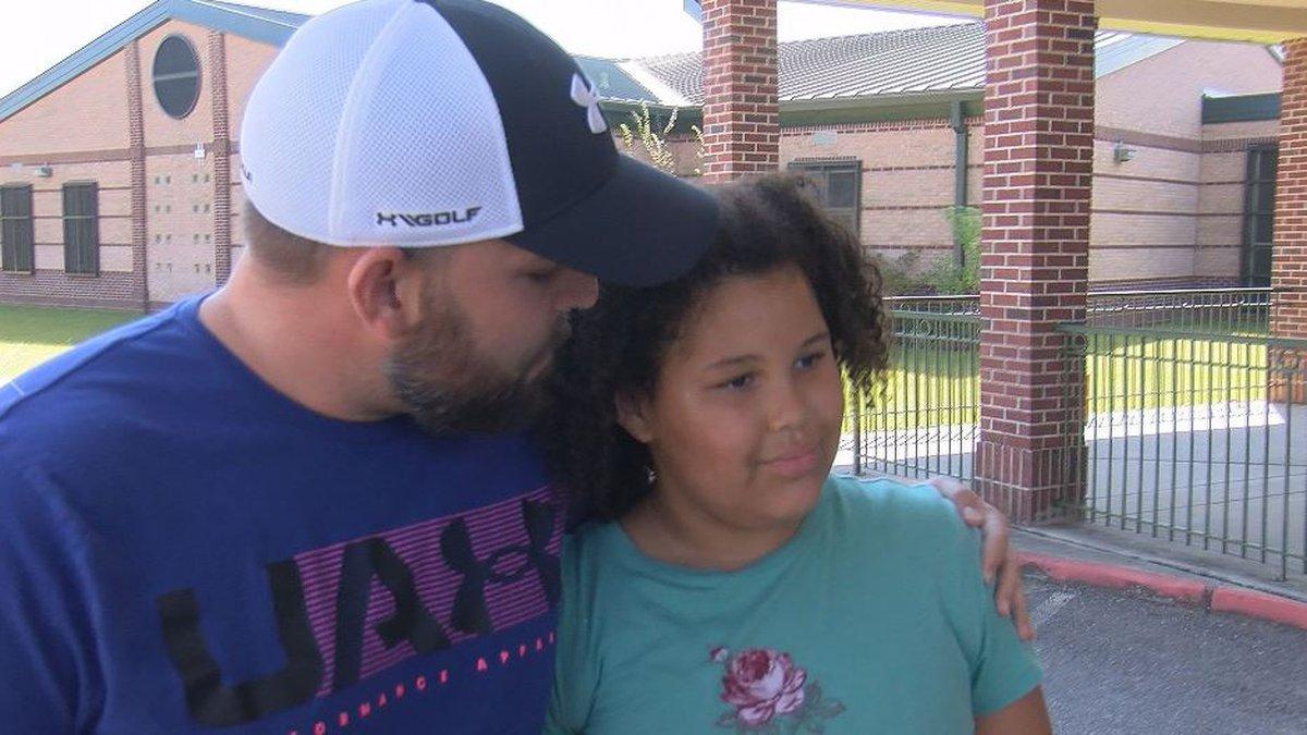 Harrison County School District bus driver Robert Morgan gives fourth-grader Ella Harper a hug...