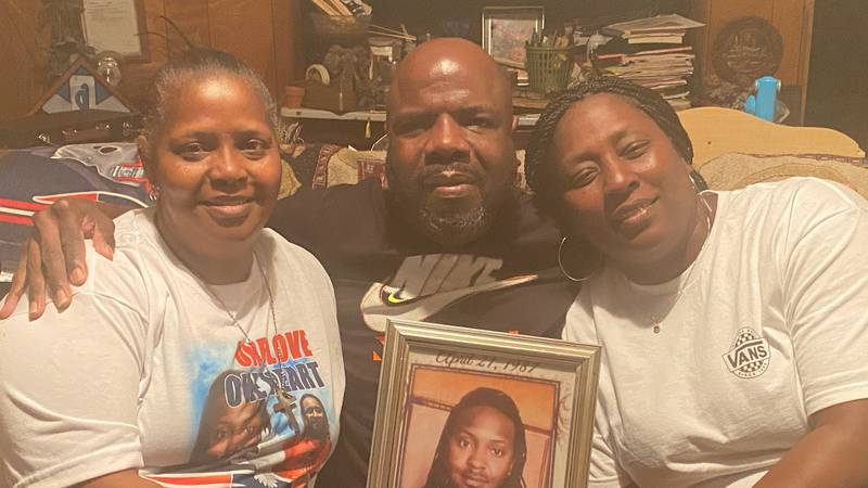 Kim Neal, Edward Cartwright and his wife Katrina, hold up a picture of Kim's son David, who was...