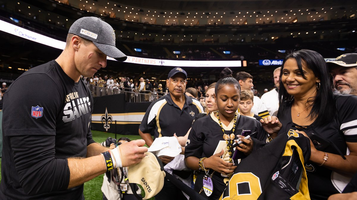 Drew Brees signs autographs for fans after warming up on the Superdome floor prior to a Saints...
