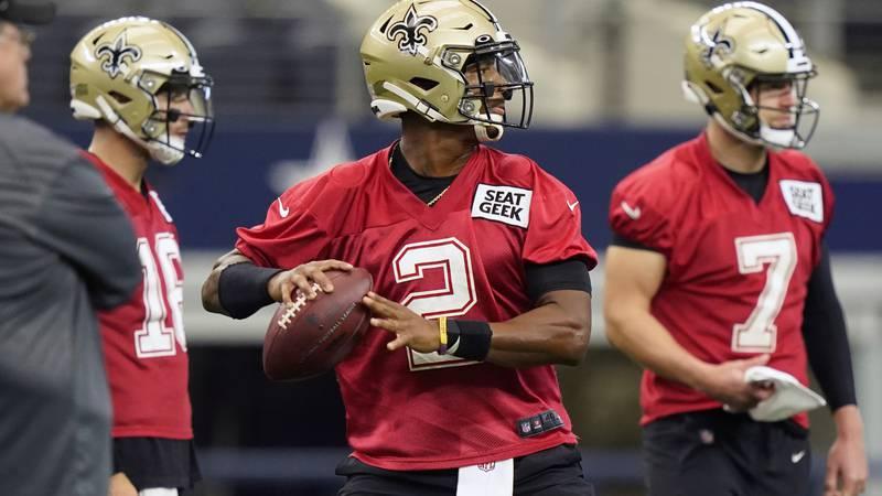 New Orleans Saints quarterback Jameis Winston (2) passes as fellow quarterbacks Taysom Hill (7)...