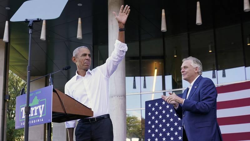 Former President Barack Obama, left, waves during a rally with Democratic gubernatorial...