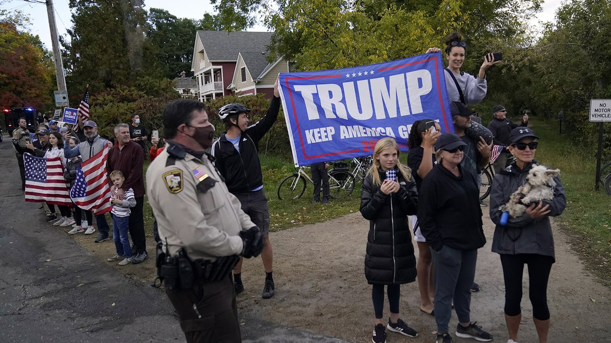 Protesters line and supporters line the route as the motorcade carrying President Donald Trump...