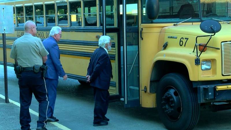 Defendant Sergio Sandoval, right, looks Tuesday at the bus he drove for the ocean Springs...