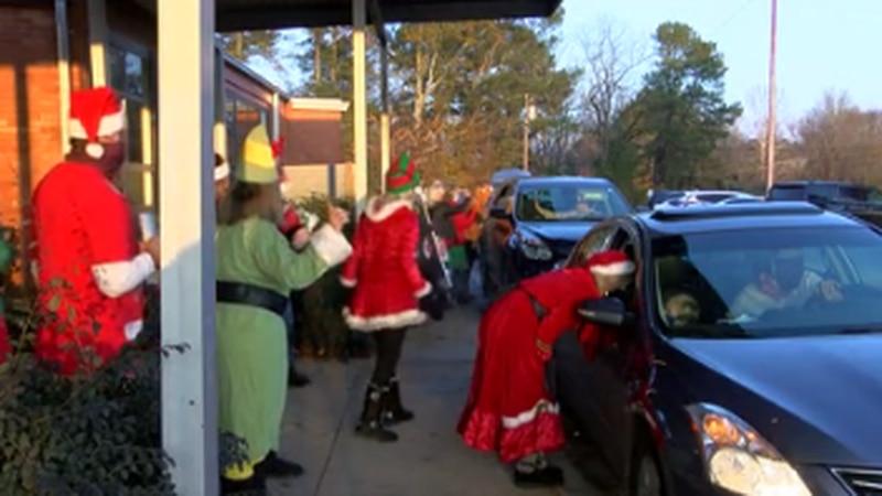 Kosciusko teachers and staff greet parents and grandparents in drive through Christmas...
