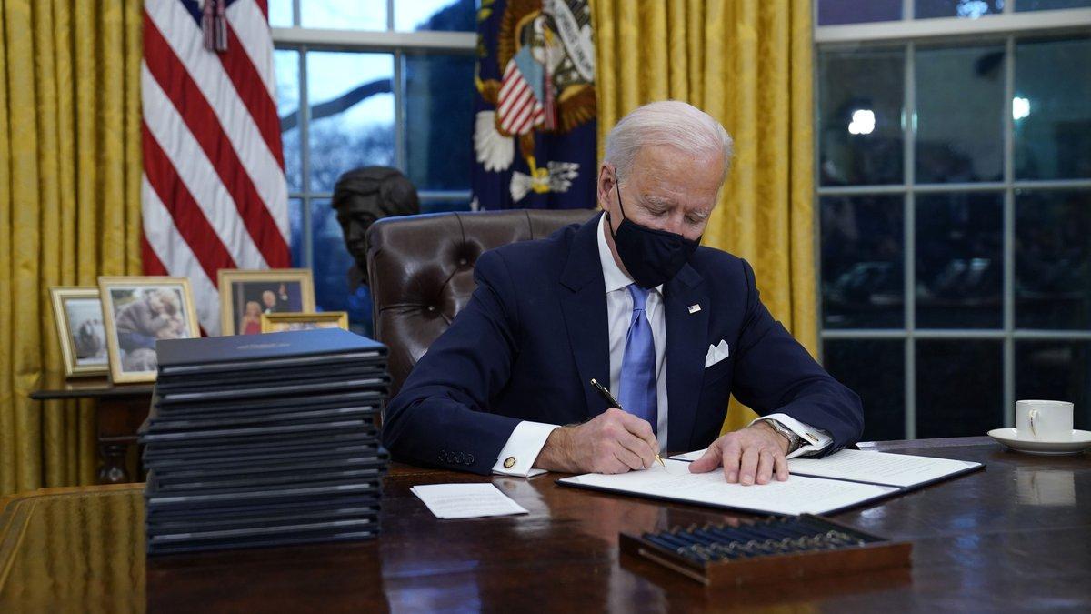 El presidente Joe Biden firma su primera orden ejecutiva en el Despacho Oval de la Casa Blanca...
