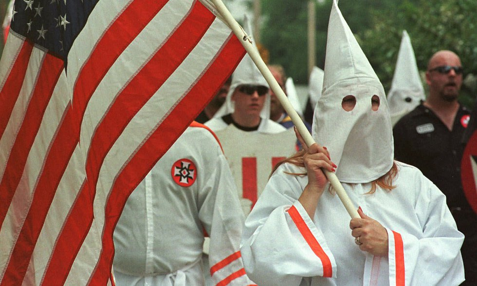 Members of the Church of the American Knights of the Ku Klux Klan march around the Madison...