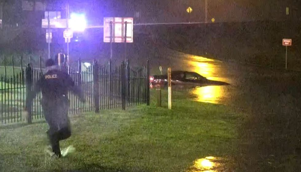 A car drowned out in floodwaters due to heavy rain at the foot of the Interstate 220 off ramp...