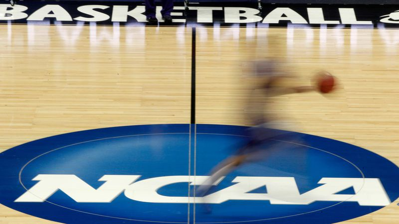 In this March 14, 2012, file photo, a player runs across the NCAA logo during practice in...