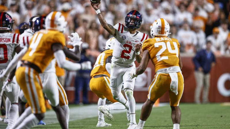 Mississippi quarterback Matt Corral (2) throws to a receiver as he's defended by Tennessee...
