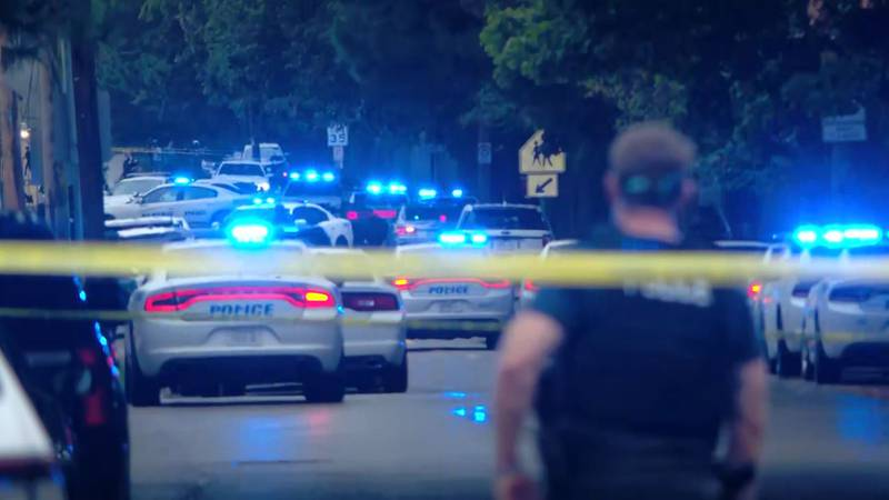 Police cars line the street outside Cummings K-8 Optional School following a shooting Thursday,...