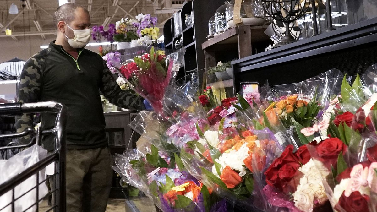 A man shops at a grocery store for flowers for Mother's Day during the COVID-19 pandemic in...