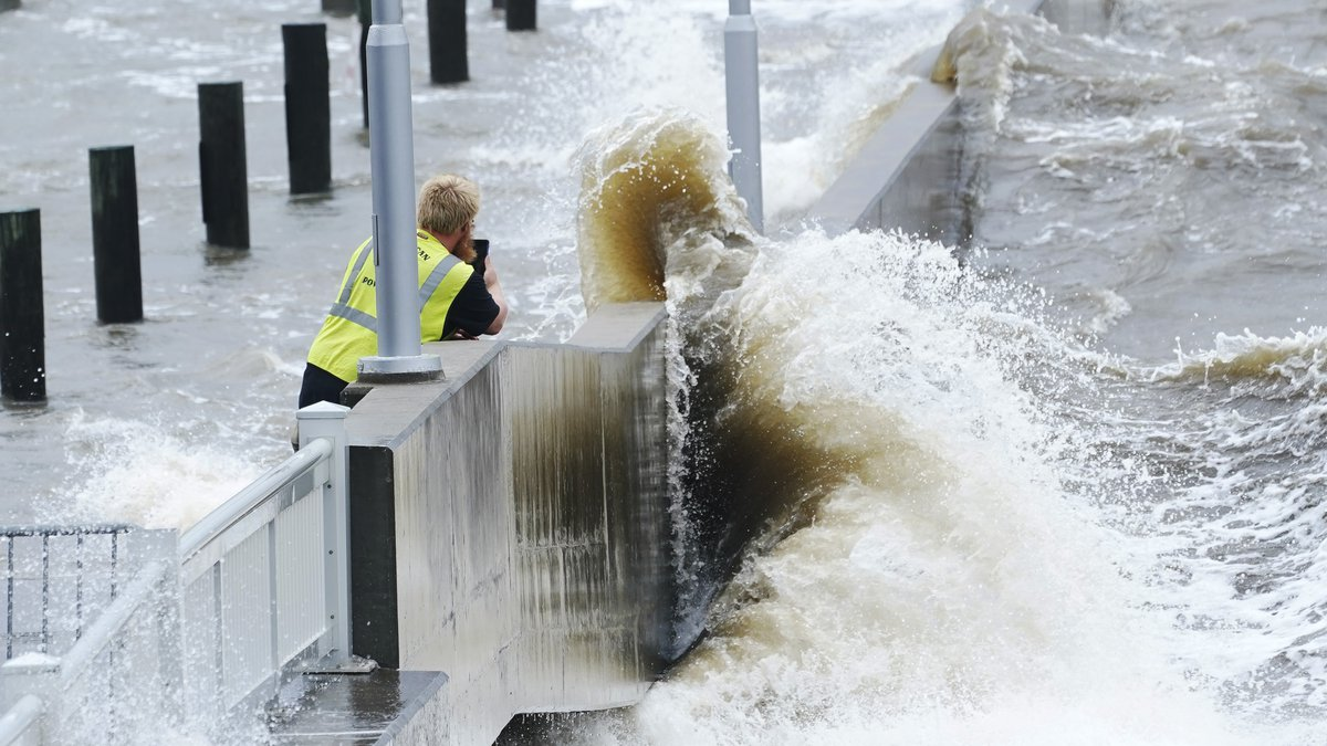 A utility worker photographs waves as they slam against a sea wall at the city marina as outer...