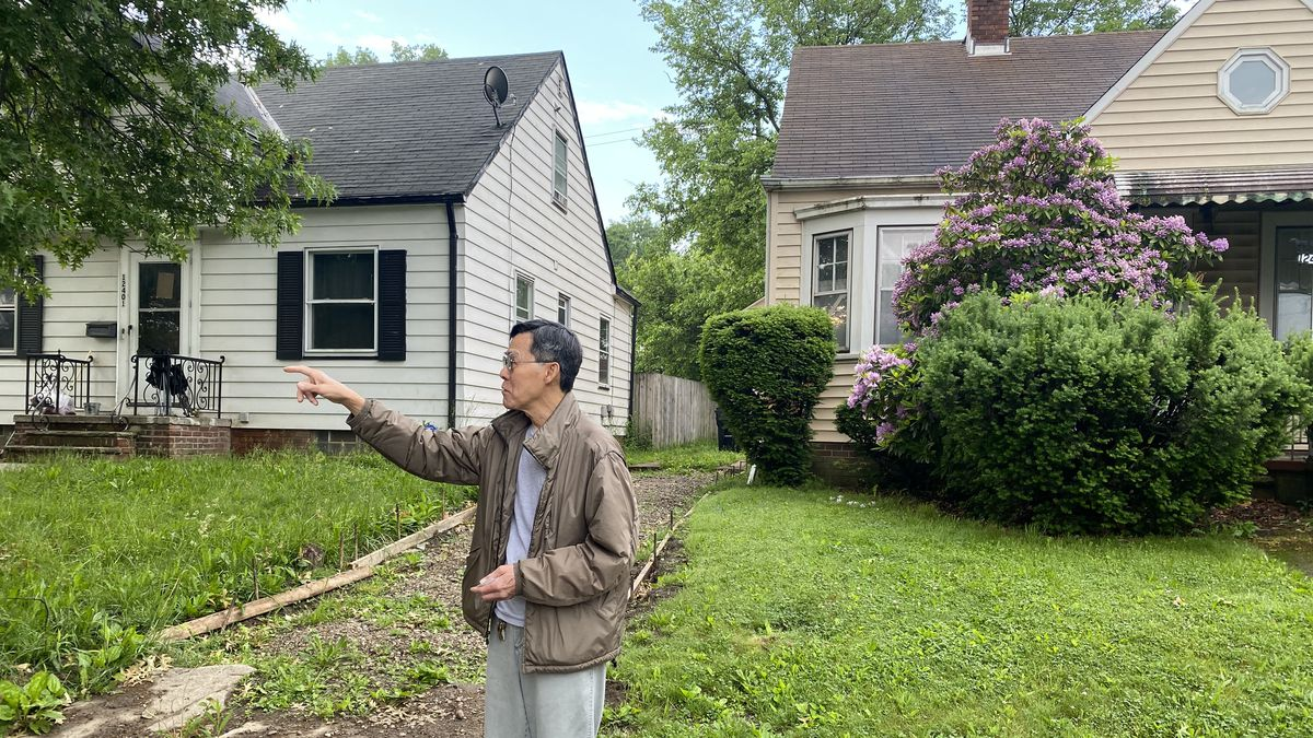 Khau Tran, standing where his driveway was, points to the house where the contractor was...