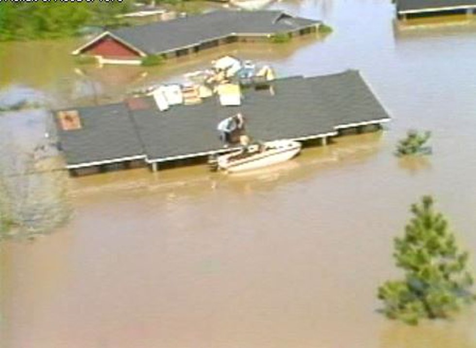 Homeowner on East Sedgwick Court moves furniture to his roof in the Great Flood of 1979...