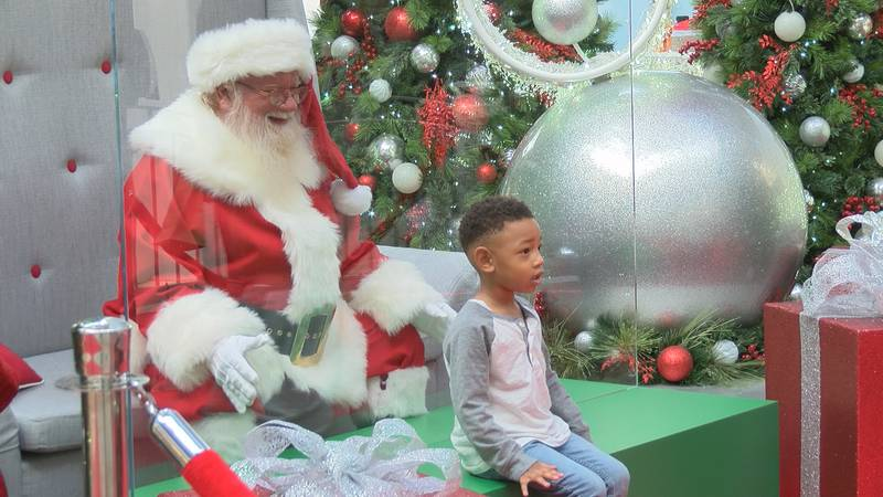 Child poses to take picture with Santa