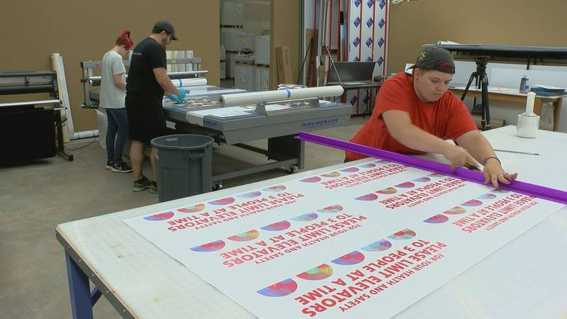 Employees at Knight Abbey Printing in Biloxi work on social distancing signs that will be put...